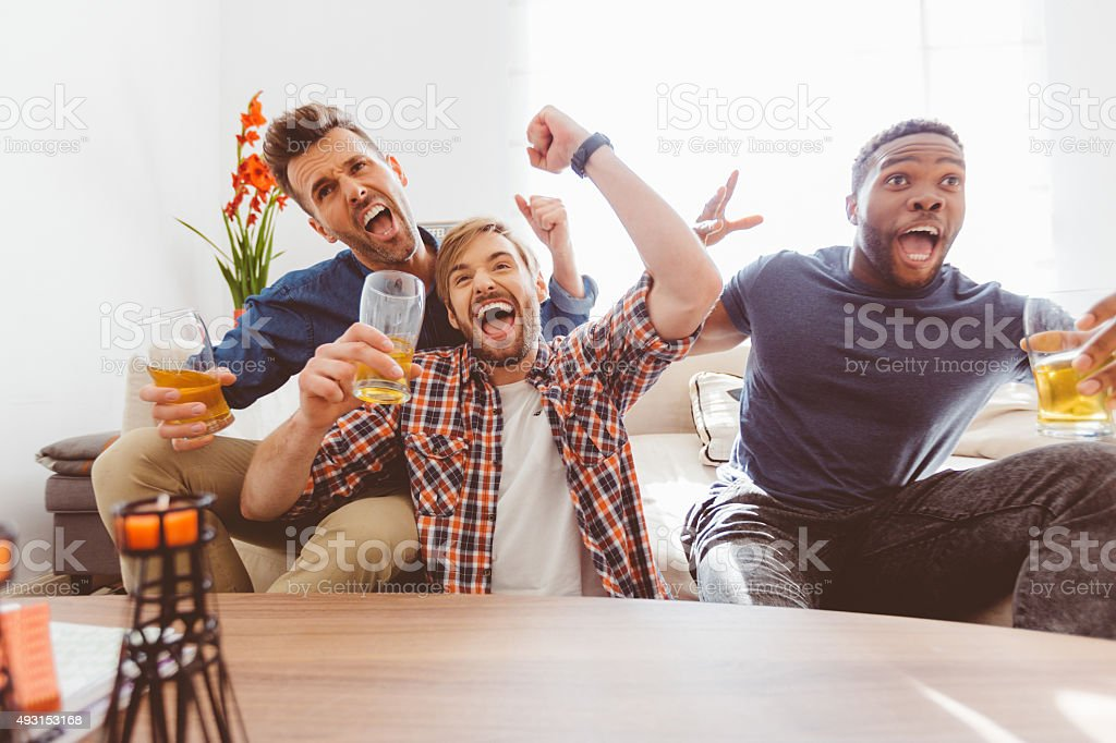 Three excited guys watching sport on tv stock photo