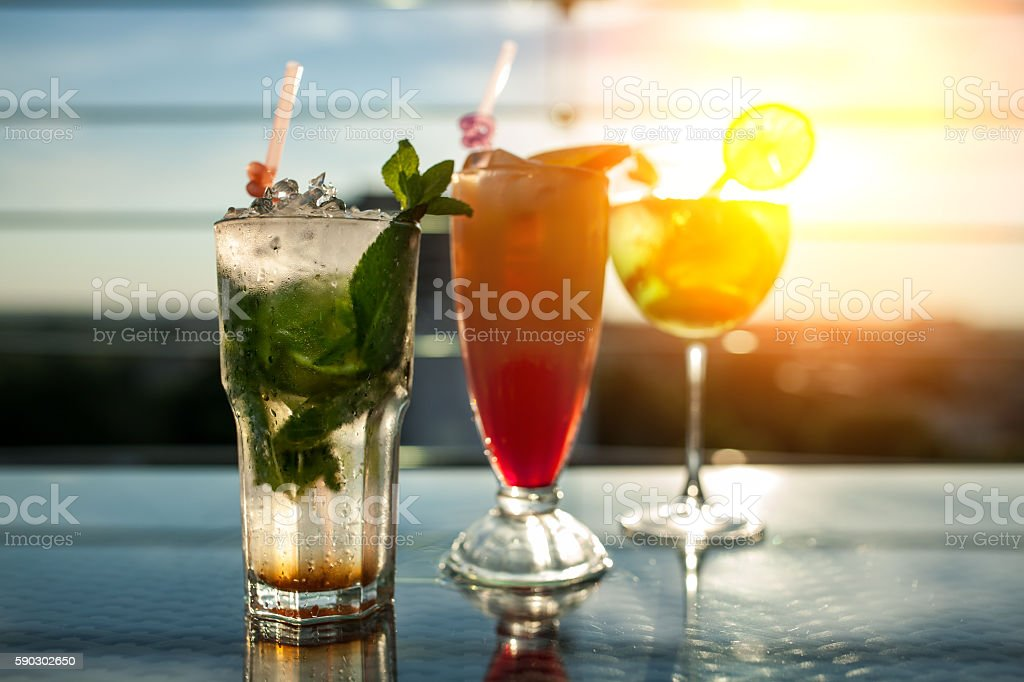 three exotic cocktails in rays of sun; stock photo