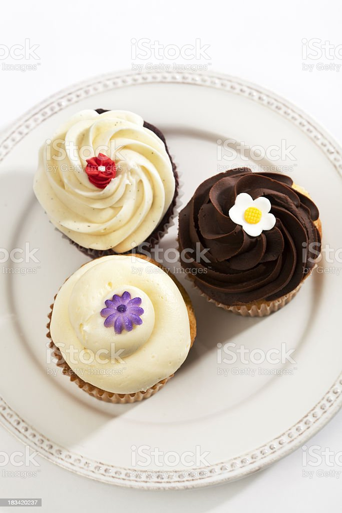 Three Fancy Frosted, Decorated Gourmet Sweet Cupcakes on White Plate royalty-free stock photo
