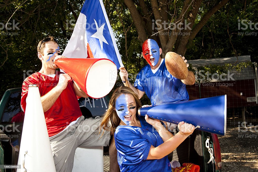 Three fans in truck at football game tailgate party. Group. royalty-free stock photo