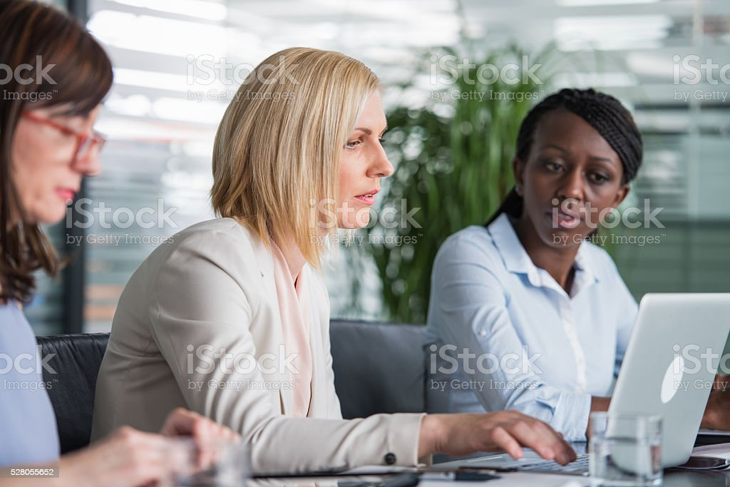 Three Female Coworkers Using A Laptop At Workplace stock photo