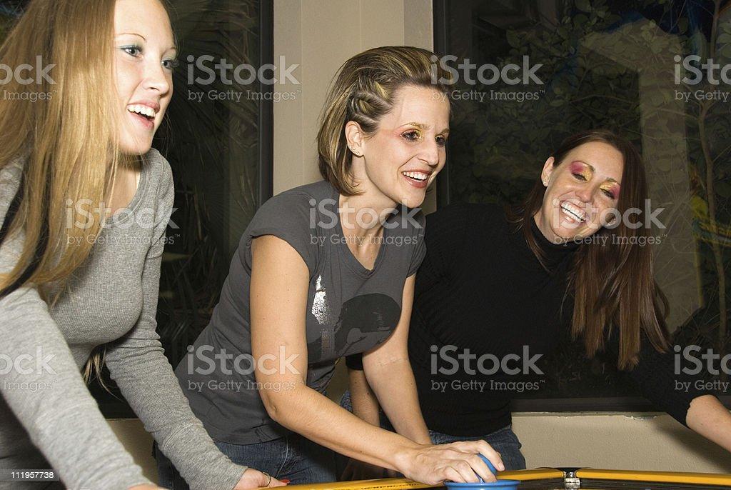 Three female friends enjoying a game of air hockey stock photo