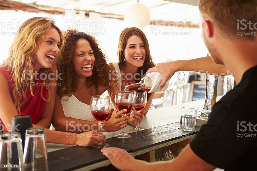 Three Female Friends Enjoying Drink At Outdoor Bar stock photo
