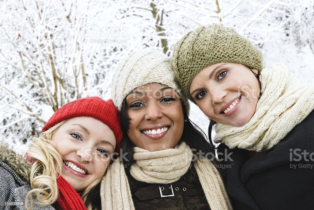Three female friends outside on a snowy winter day royalty-free stock photo