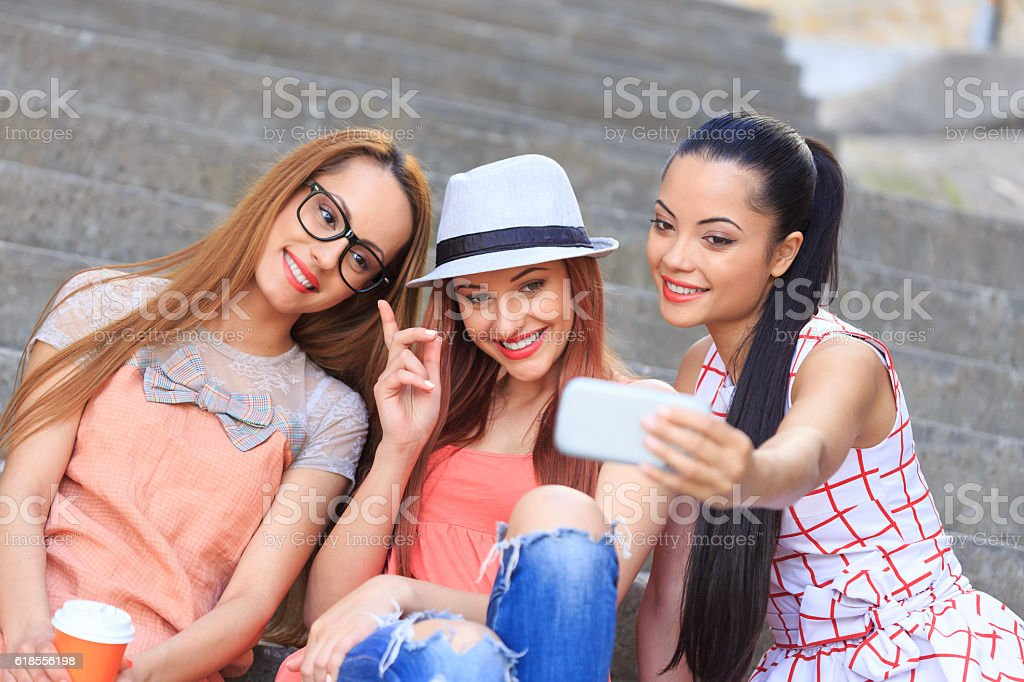 Three female friends sitting on stairs and making selfie stock photo