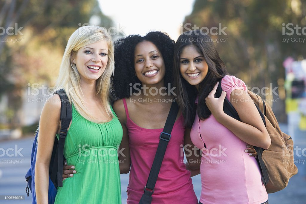 Three female friends smiling and posing stock photo