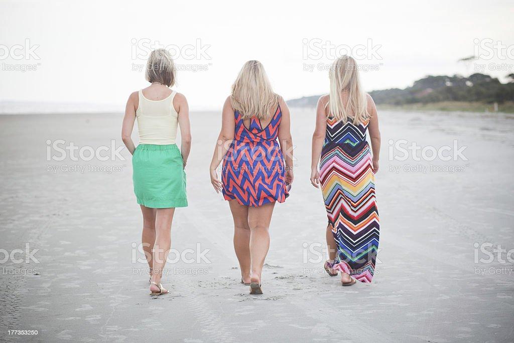 Three female friends walk on the beach at dusk royalty-free stock photo