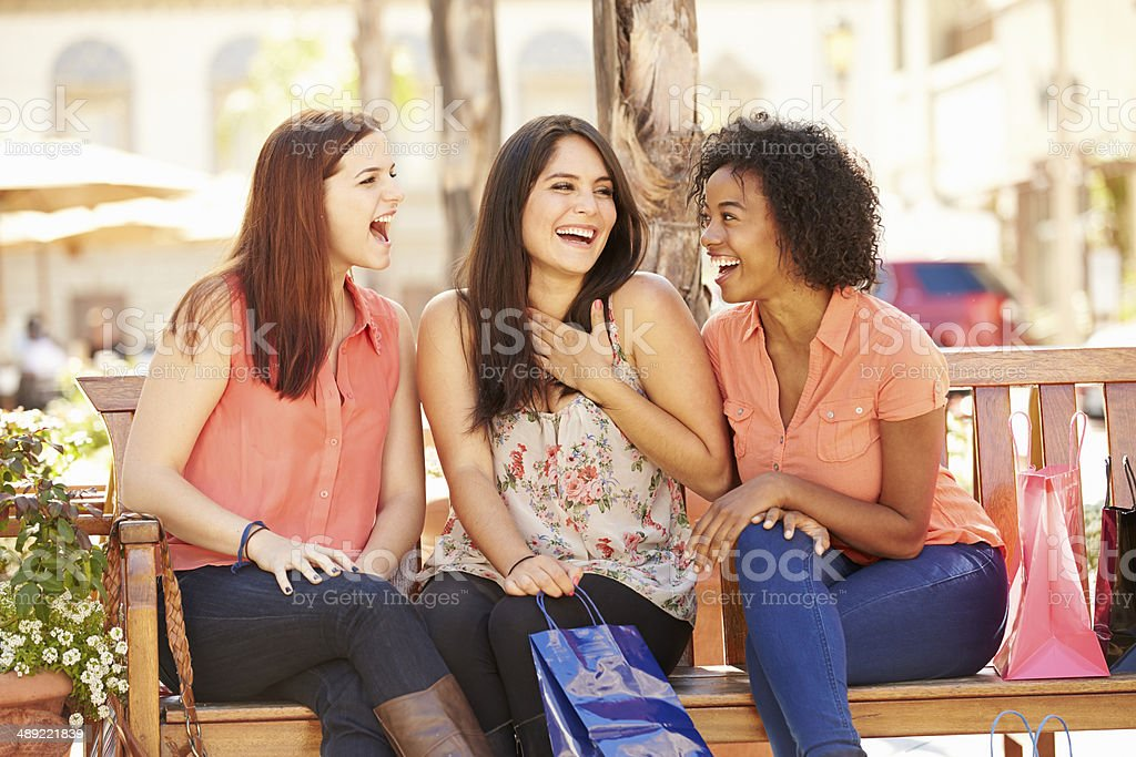 Three Female Friends With Shopping Bags Sitting In Mall royalty-free stock photo