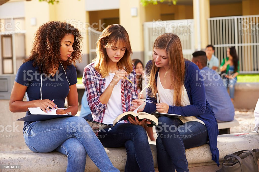 Three Female High School Students Working On Campus stock photo