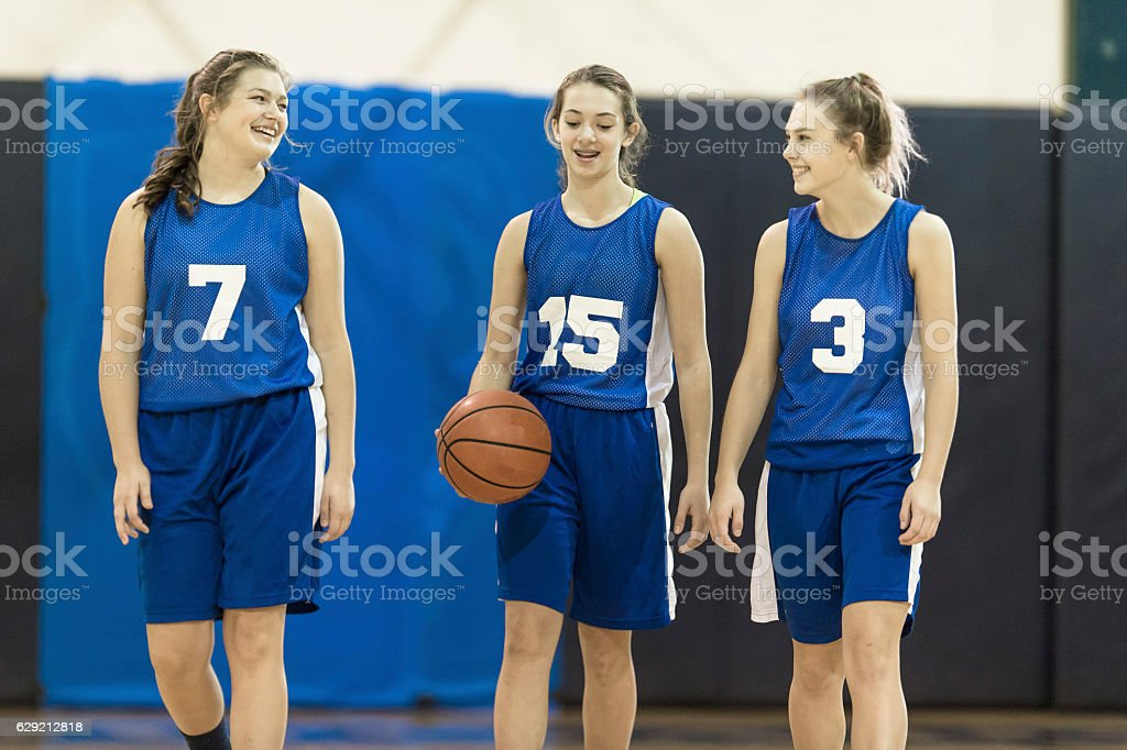 Three female teenage basketball players walking together stock photo