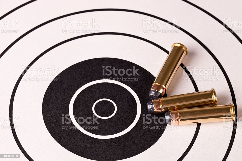 Three Fifty Seven bullets laying on target with Bulls Eye stock photo