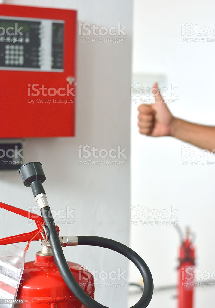 Three Fire Extinguishers, Fire Alarm Box and Thumb´s Up Sign stock photo