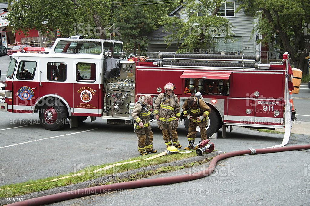 Three Firefighters on Scene of House Fire stock photo