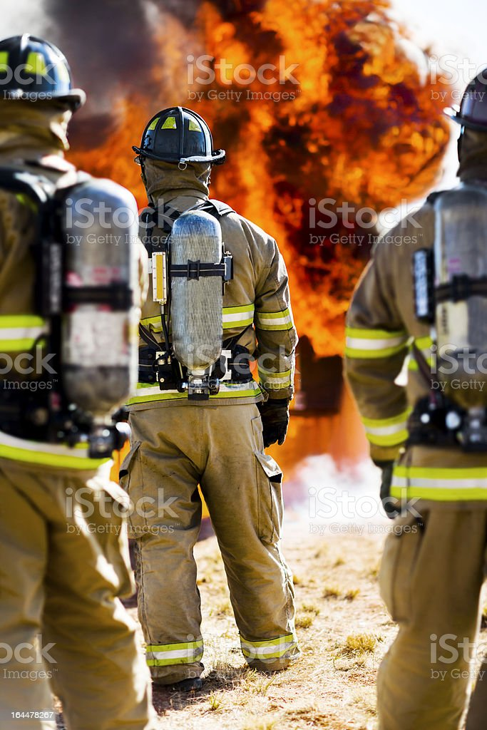 Three Firefighters Watching Blazing Fire royalty-free stock photo