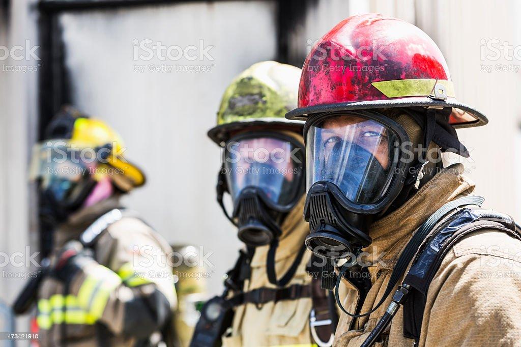 Three firefighters wearing oxygen masks stock photo