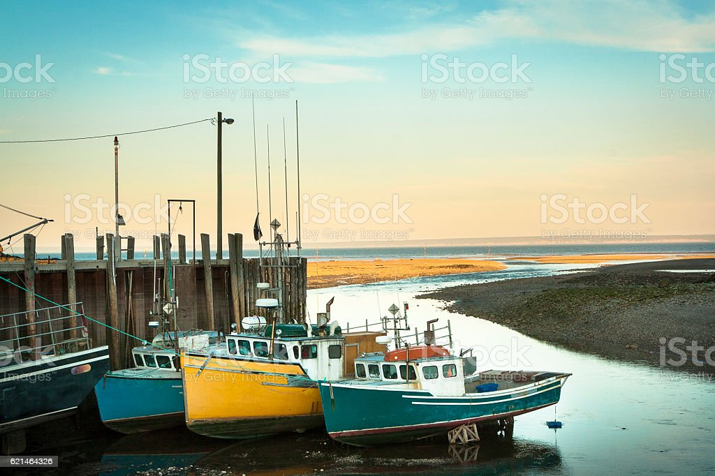 Three fishing boats docked at low tide stock photo
