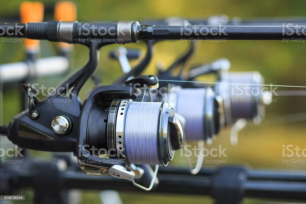 Three fishing rods with reel set up on holder stock photo