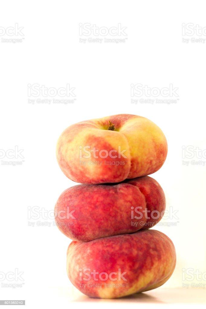 Three Flat Donut/Saturn Peaches Stacked, White Background stock photo