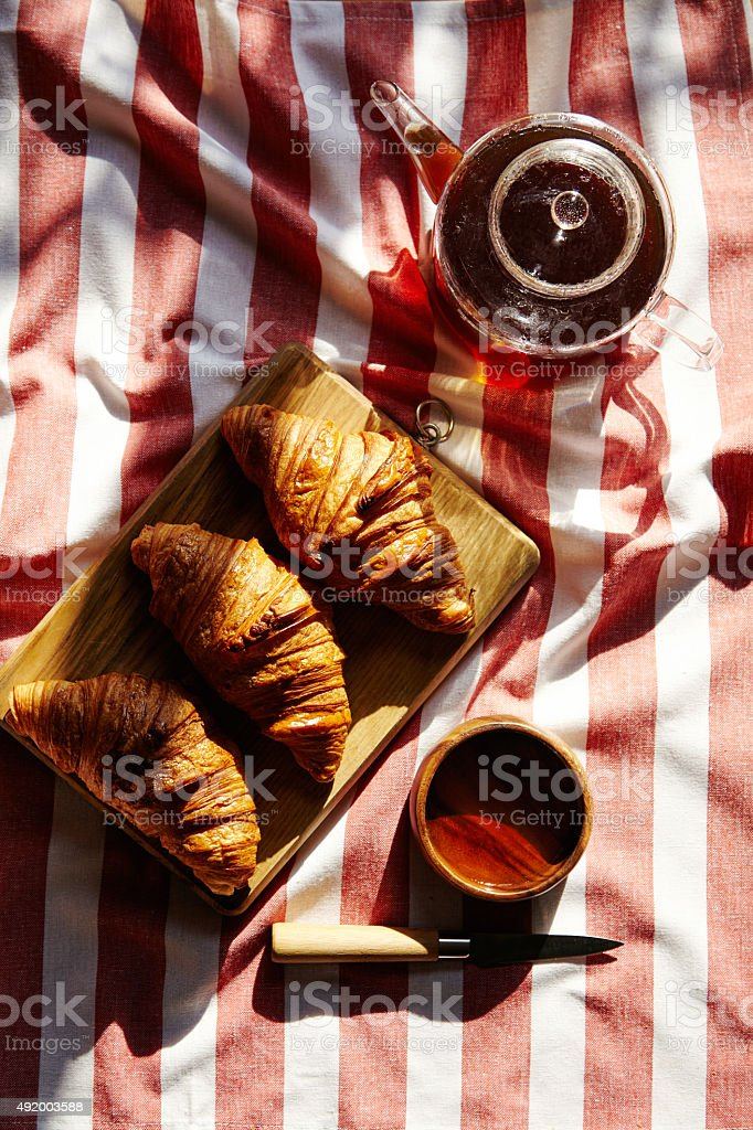 Three french freshly baked croissants on wooden plate with teapo stock photo