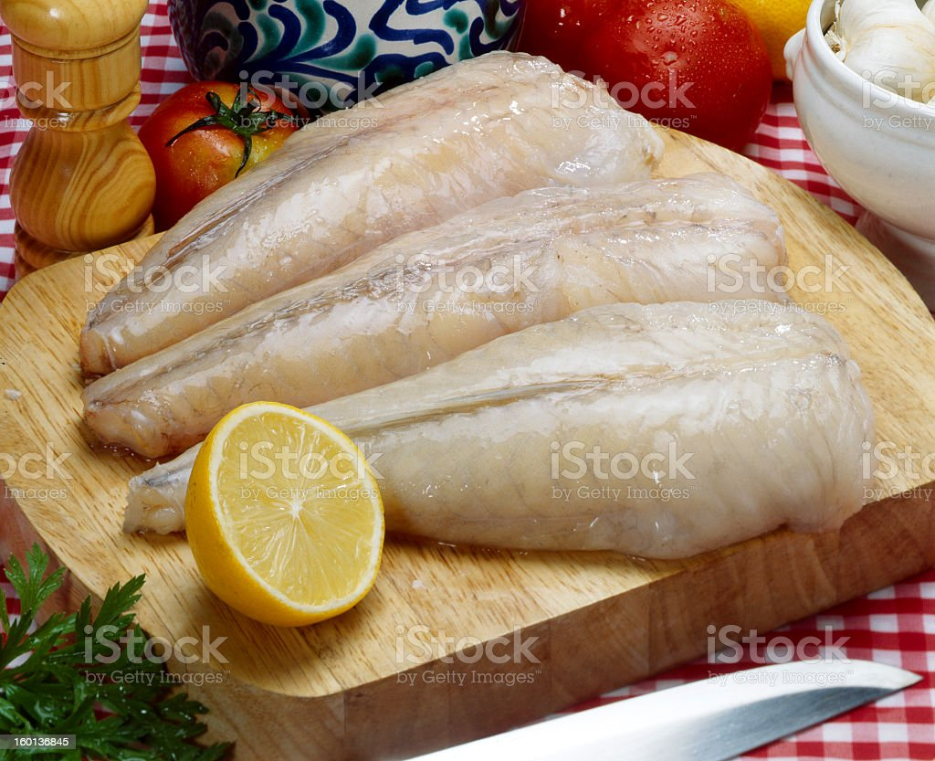 Three fresh fish fillets with lemon on wooden chopping board stock photo