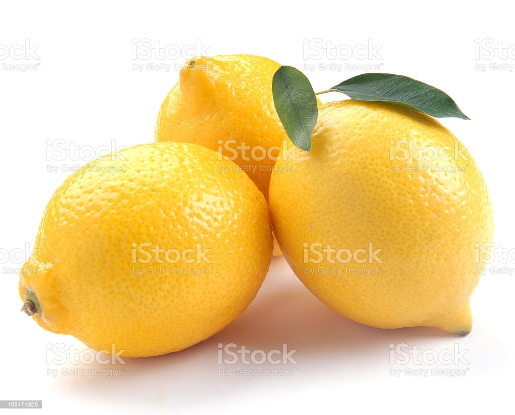 Three fresh lemons gathered on a white table royalty-free stock photo