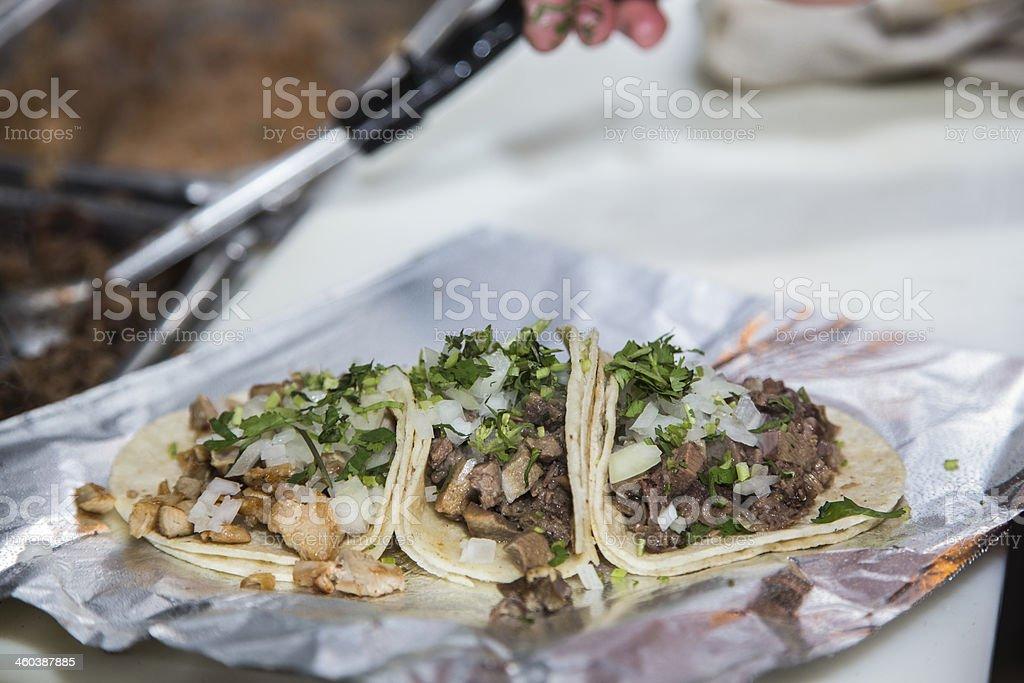 Three freshly prepared tacos on foil stock photo