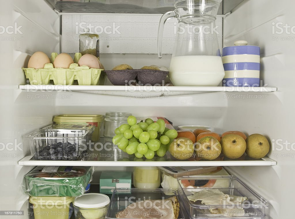 Three fridge shelves full of food stock photo
