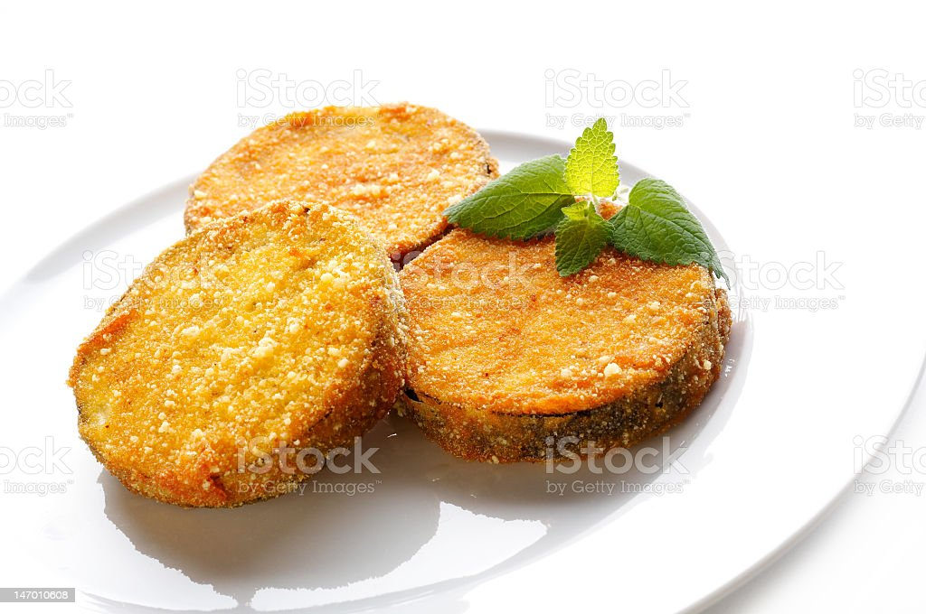 Three fried aubergine slices on a white plate royalty-free stock photo