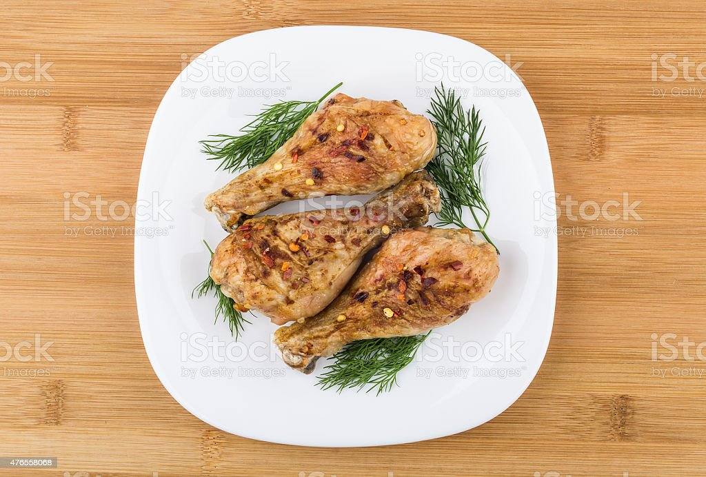 Three fried chicken legs sprinkled pepper with dill in plate stock photo