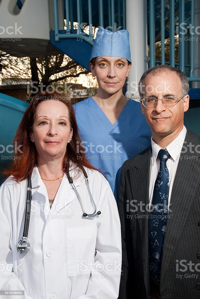 Three friendly doctors standing in front of a playground royalty-free stock photo