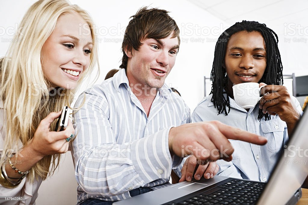 Three friends are amused by something on a laptop royalty-free stock photo