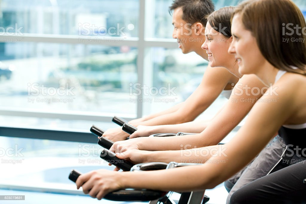 Three Friends Are In A Spinning Class At A Gym stock photo