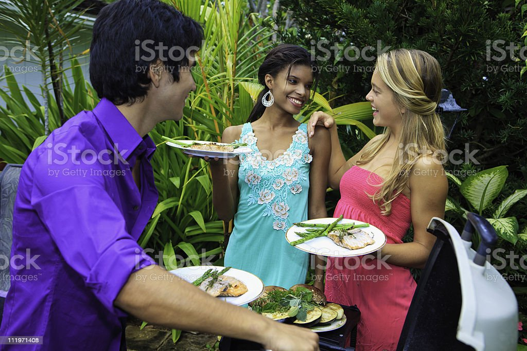 three friends at a barbecue party royalty-free stock photo