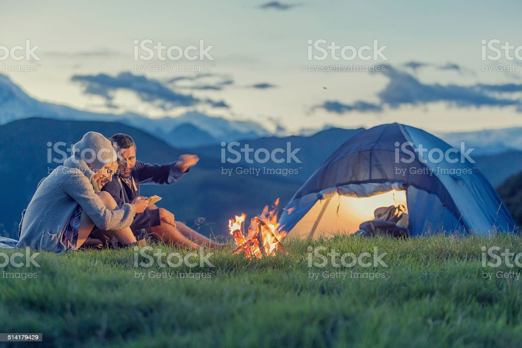 Three friends camping on mountain at sunset stock photo