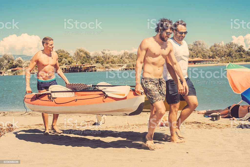 three friends carrying canoe stock photo