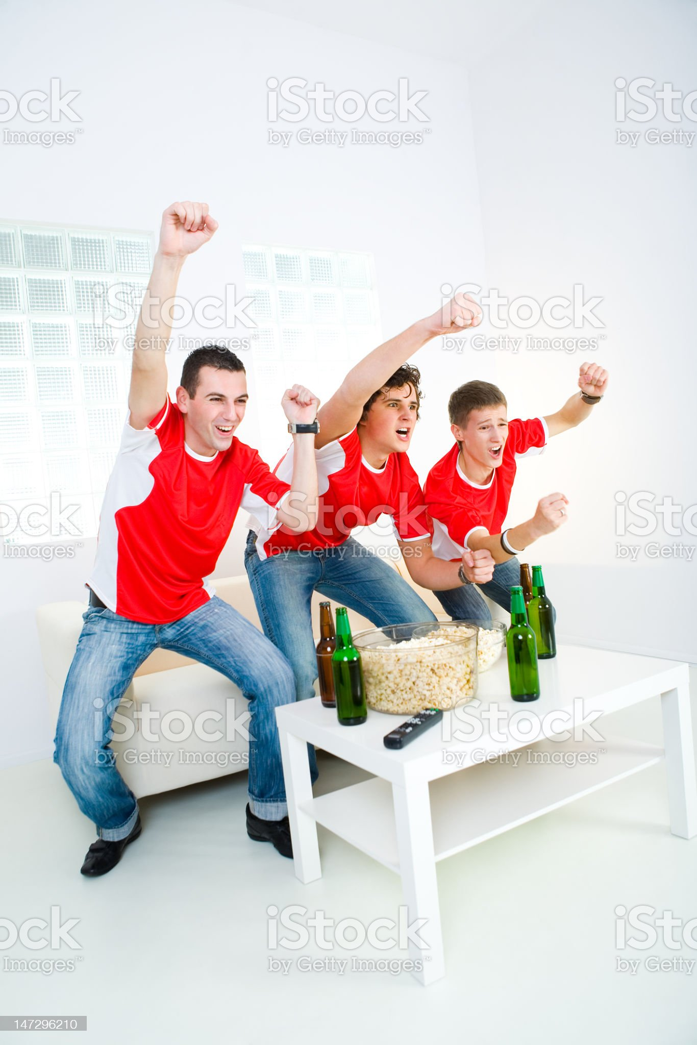 Three friends celebrate their favored sports team's victory royalty-free stock photo