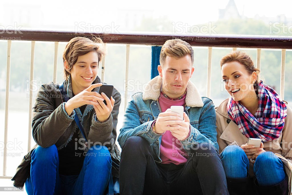 Three friends discussing media on their phones stock photo