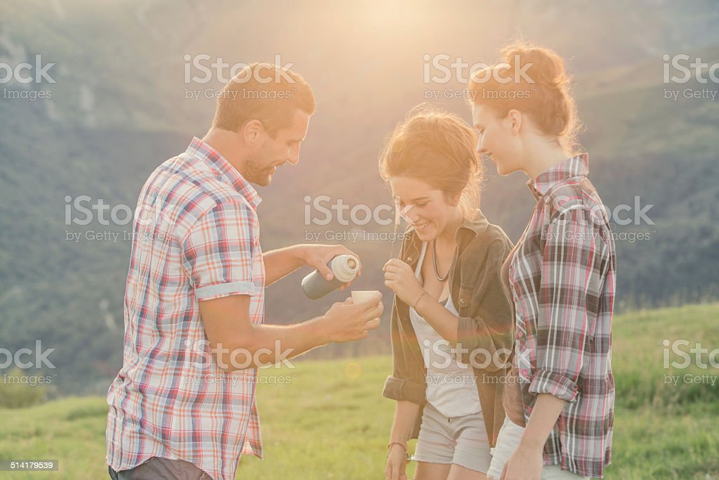Three friends drinking hot tea on mountain at sunset stock photo