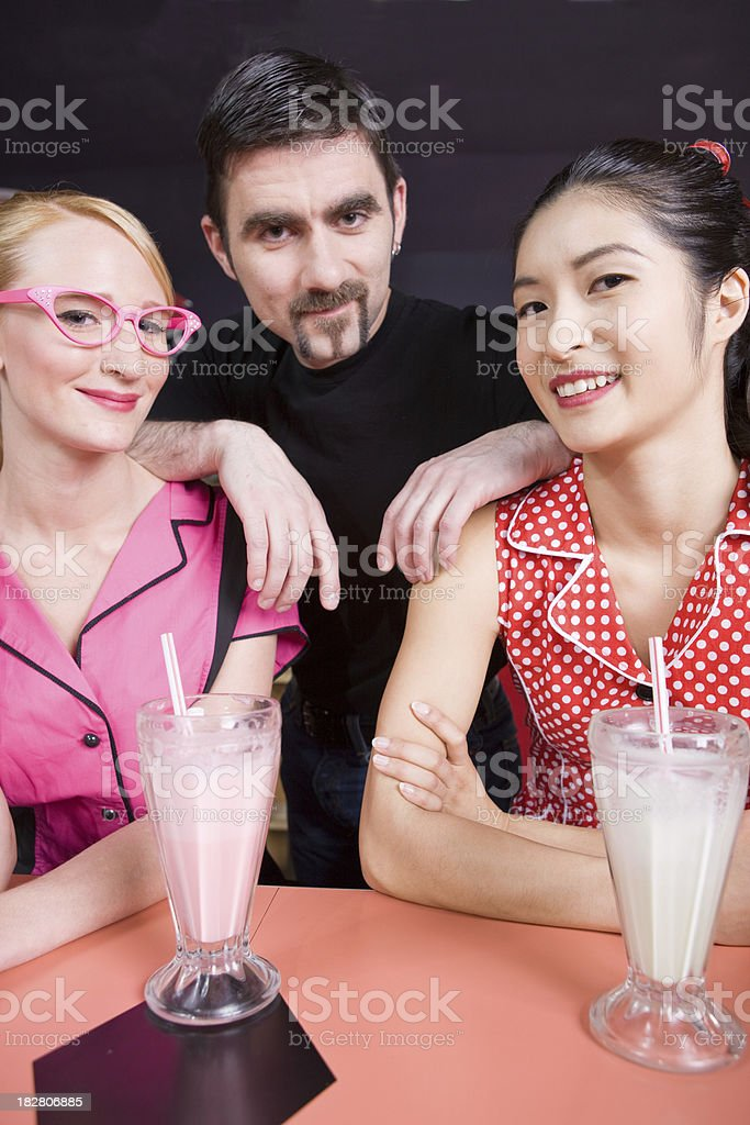 Three Friends Enjoying Shakes At The Local Diner royalty-free stock photo