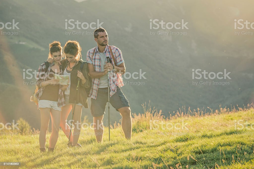 Three friends have rest looking map on mountain stock photo