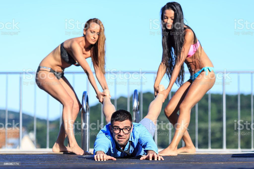 Three friends having fun at swimming pool stock photo