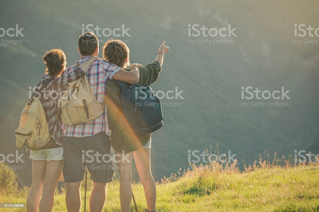 Three friends hug themselves looking panorama on mountain at sunset stock photo