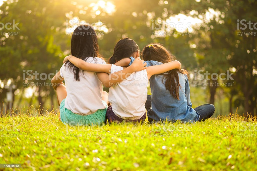 Three friends hugging while sitting in a grass field stock photo