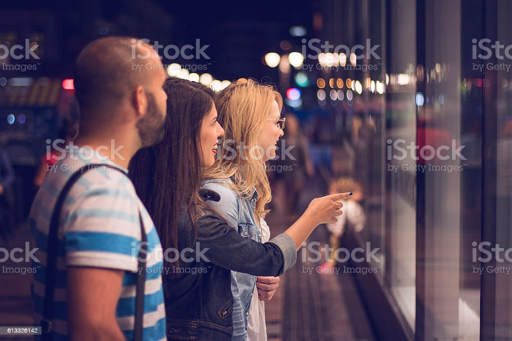 Three friends in the evening shopping stock photo