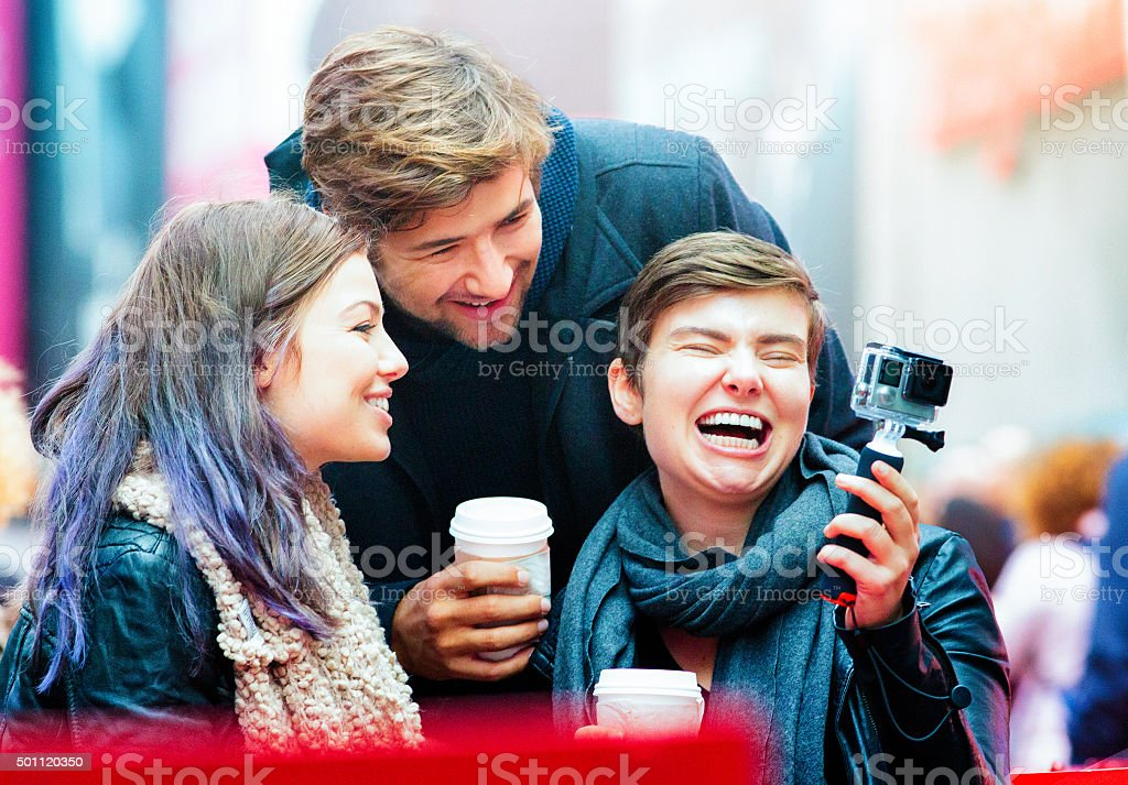 Three friends laugh watching footage on action camera stock photo
