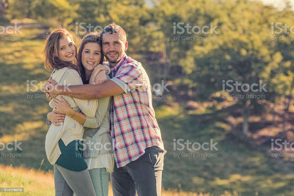 Three friends looking at camera hug themselves on sunset outdoor stock photo