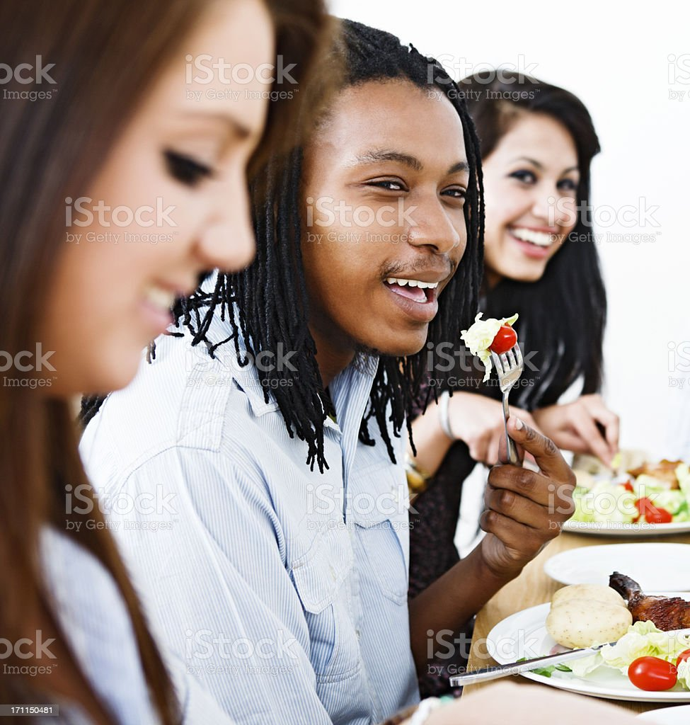 Three friends or colleagues smile as they share a meal royalty-free stock photo