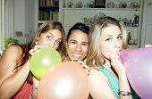 Three friends posing with balloons