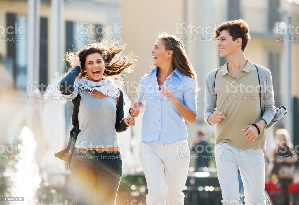 Three friends running down the streets of a city. royalty-free stock photo