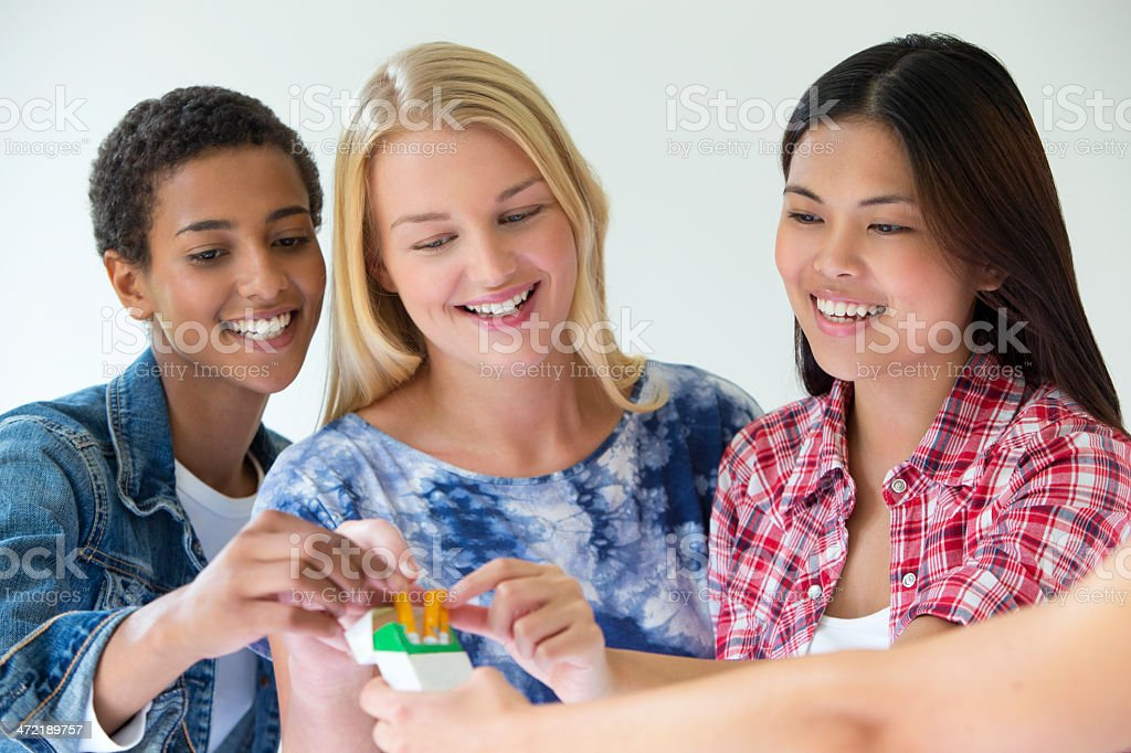 Three Friends Sharing a Pack of Electric Cigarettes royalty-free stock photo